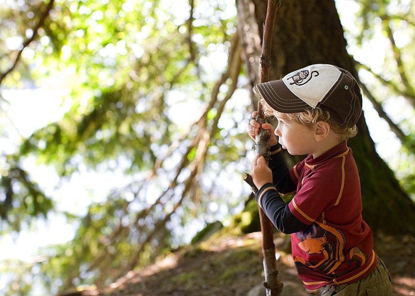 Curly-haired toddler exporing the woods. Why I delay formal learning until age 8.