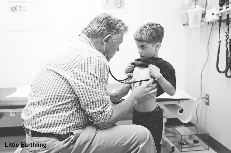 doctor listening to child's chest with stethoscope .