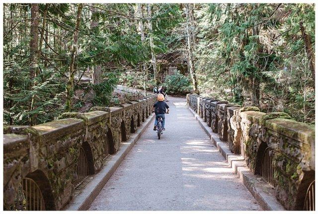 Apollo riding his bike over the bridge at Whatcom Falls Park.