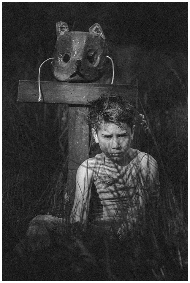 Boy sitting by grave in Pet Sematary with animal mask.