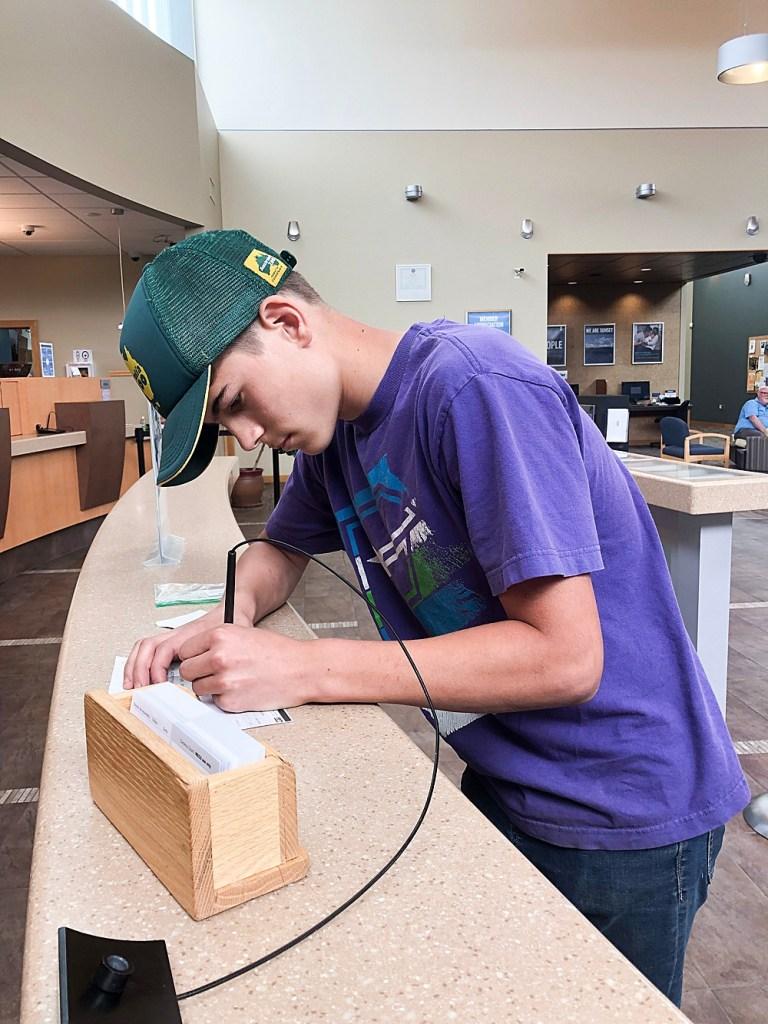 Tucker depositing his paycheck at the bank.