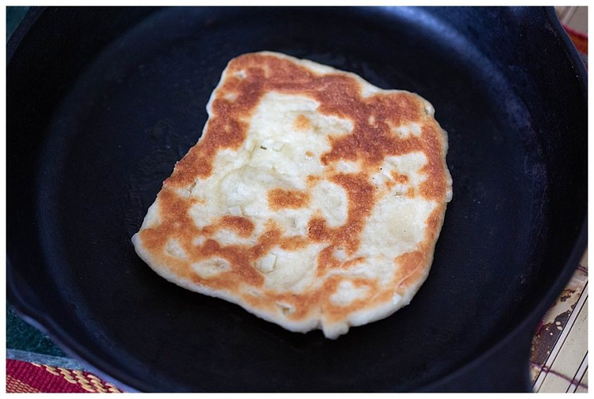 Naan bread is cooked on a skillet rather than baked in an oven.