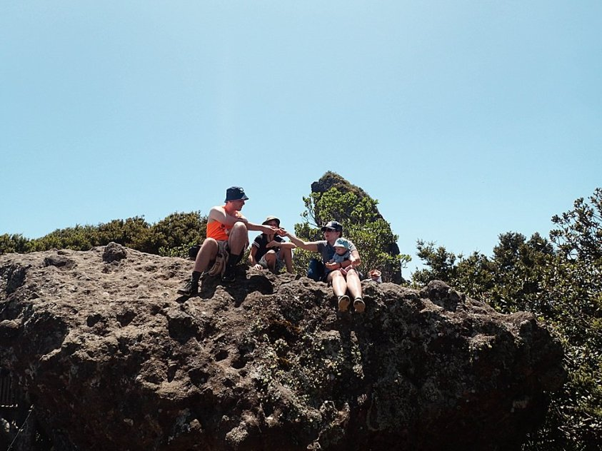 Tilly, Jared, Apollo, and Abel having lunch on the rocks in New Zealand.