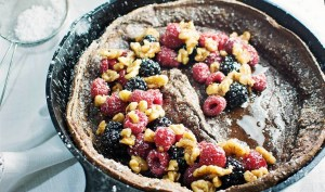 Enjoy a decadent breakfast or dessert with this Chocolate Dutch Baby served with fresh fruit and drizzles of warmed maple syrup and toasted walnuts! Get the recipe at LittleFiggyFood