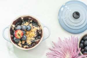 A mixed berry cobbler dessert on a white background with pink flower and blue lid