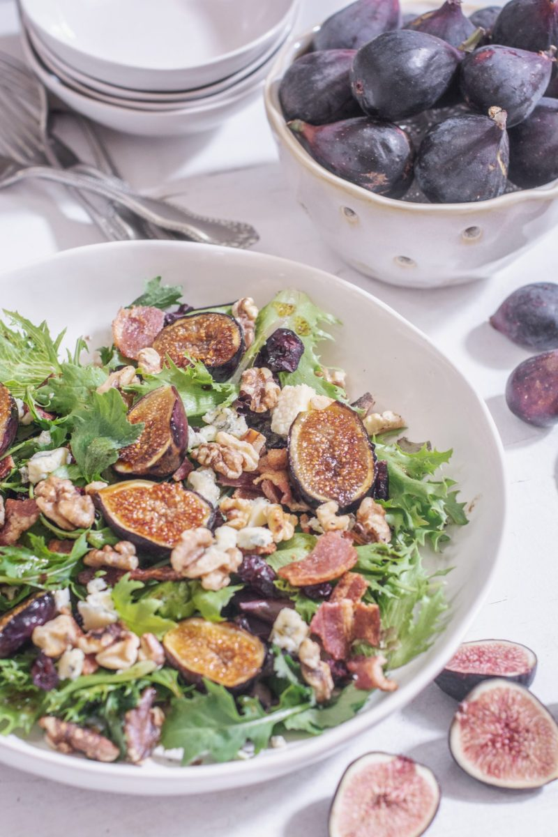 Fresh Grilled Fig Salad in large white bowl with a bowl of figs to the side.