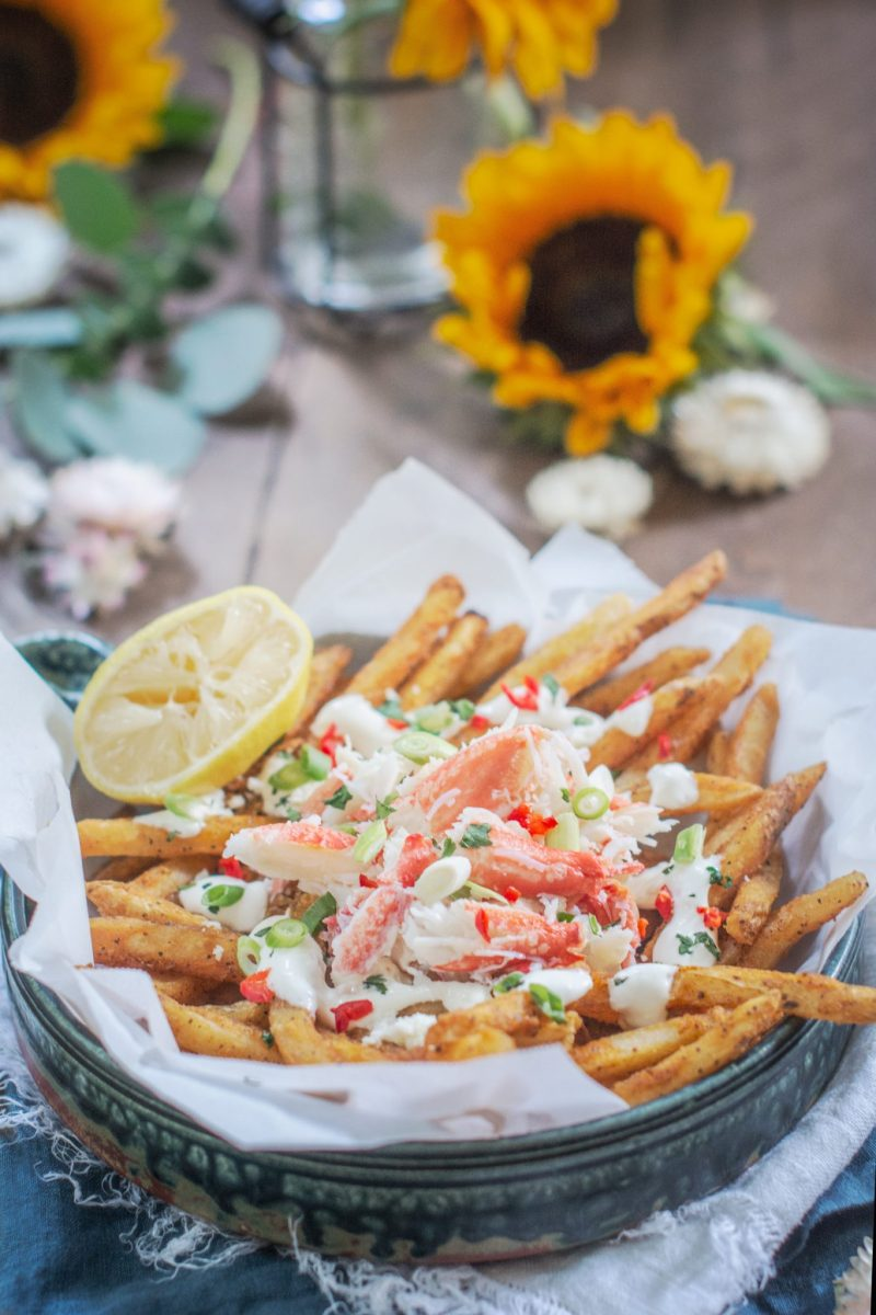 Loaded Crab Fries on brown table with sunflowers in the background
