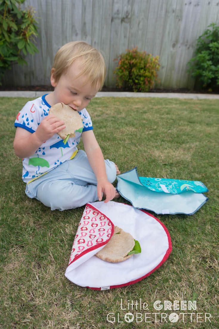 Boy eating from a sandwich wrap. Sandwich wraps are a great zero waste food storage alternative when packing for picnics.