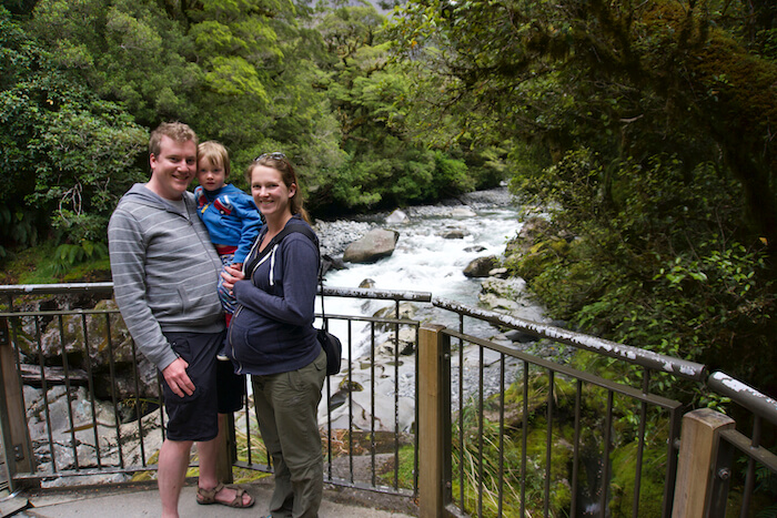 The author, her husband and eldest child pose in front of a waterfall. They were travelling in Fiordland National Park, New Zealand while she was pregnant.