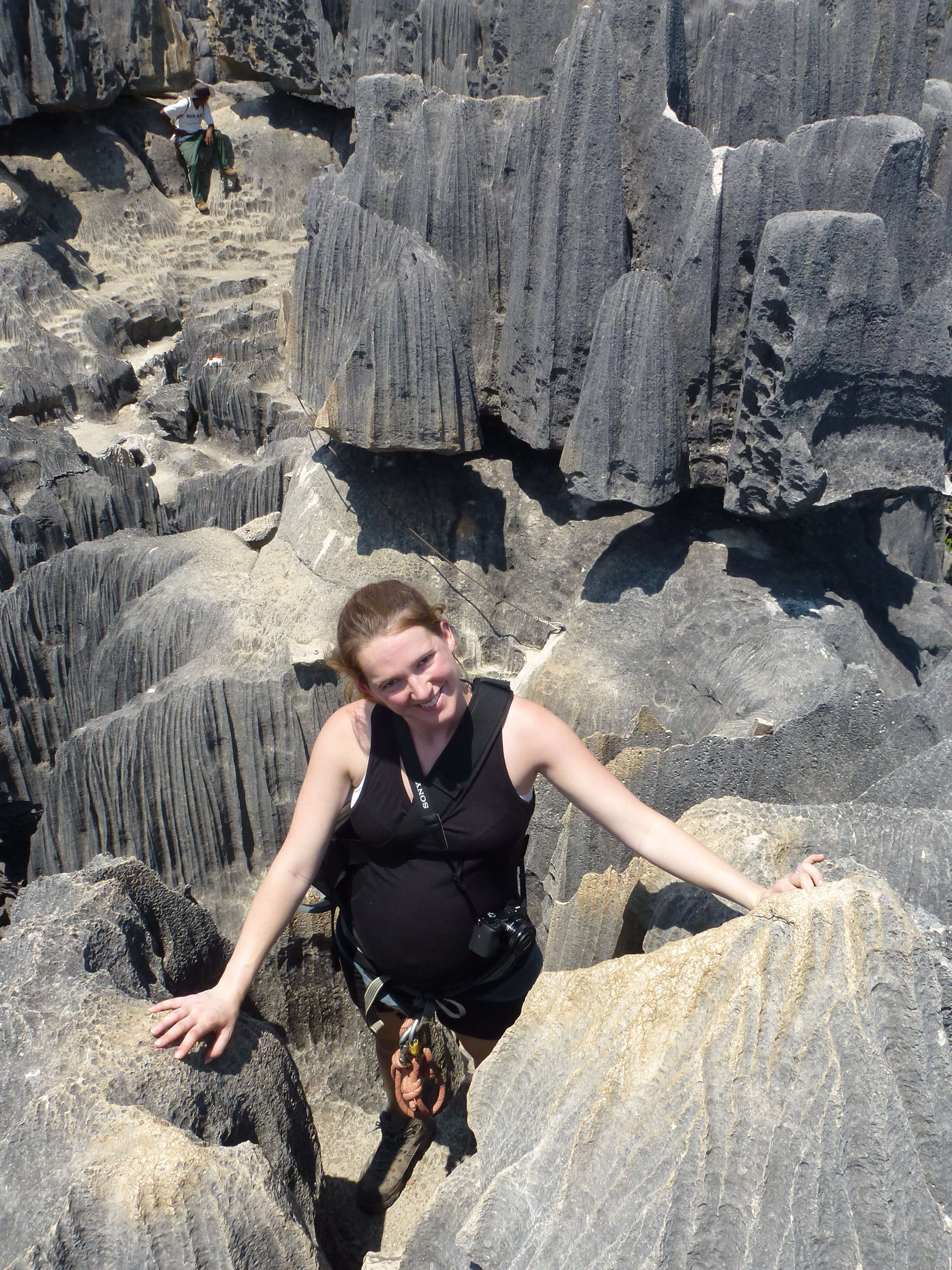 The author is wearing a harness and climbing through tsingy (limestone rocks) in Madagascar. Adventurous activities and travelling while pregnant is possible but check with your care provider first.