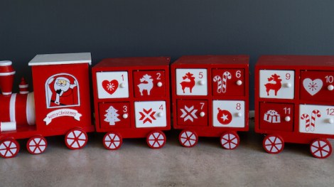 A red and white train wooden reusable advent calendar with doors for each day.