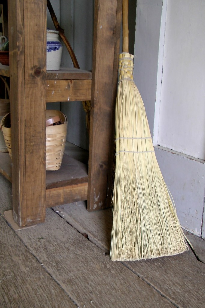 A corn broom resting against a shaker cabinet.