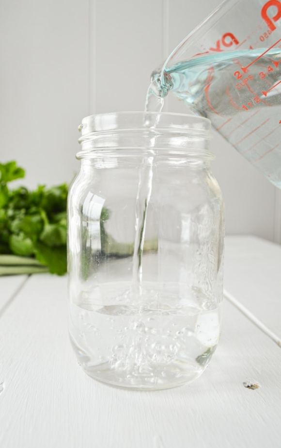 Pouring water into a glass jar.