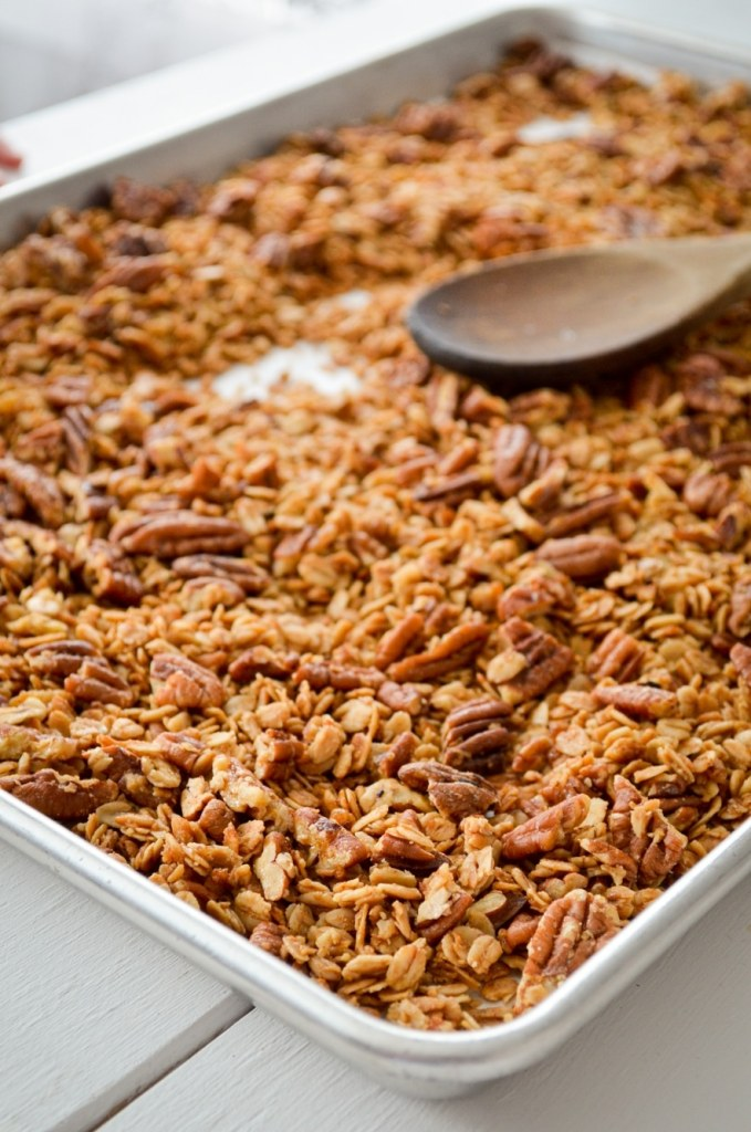 A sheet pan, filled with butter pecan granola, and a wooden stirring up the granola.