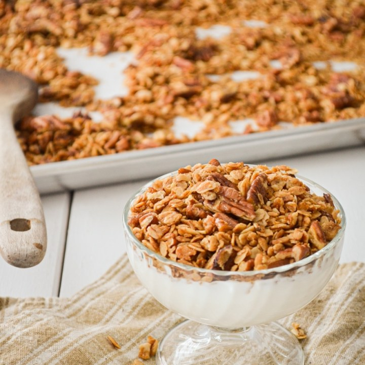 A yogurt parfair, topped with granola. A sheet pan of granola in the background, with a wooden spoon.