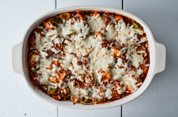 A casserole of tortellini, tomato sauce, and cheese is baked in a 9X13 pan on a white wood background.