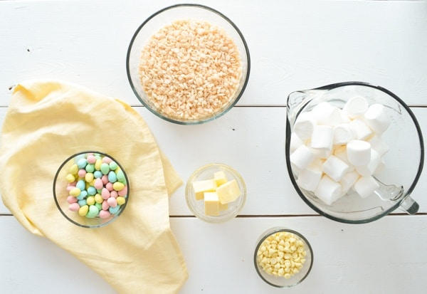 An overhead shot of a white table. Bowls contain: cadbury mini eggs, cubed butter, white chocolate chips, marshmallows, and rice krispies.