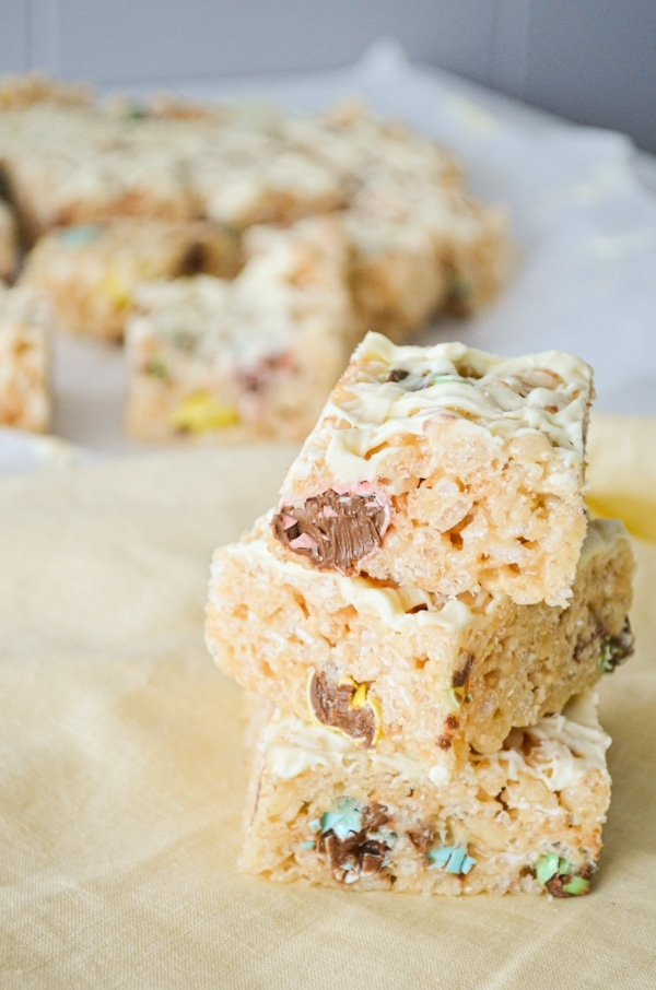 Three Easter Rice Krispie treats are stacked on top of each other. The rest are in the background in the far upper left.