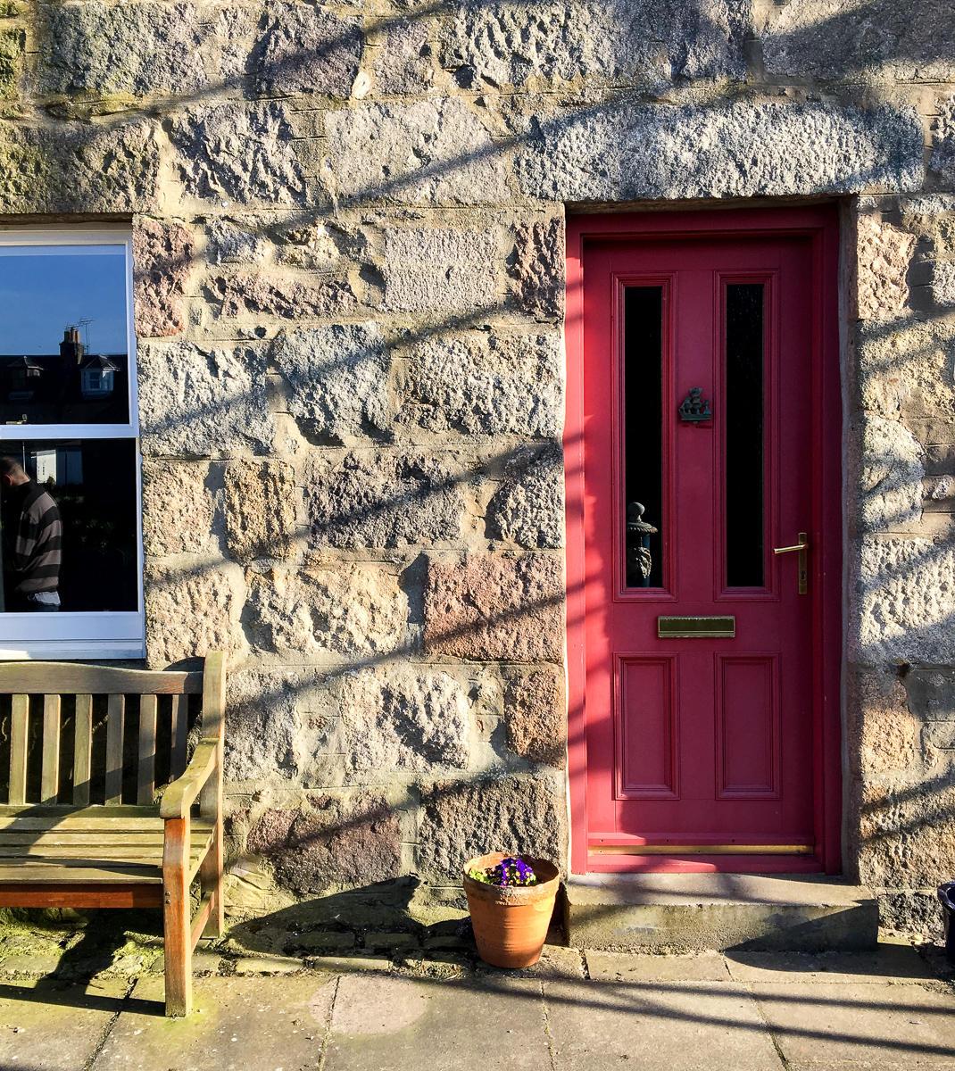 pink front door at footdee, aberdeen