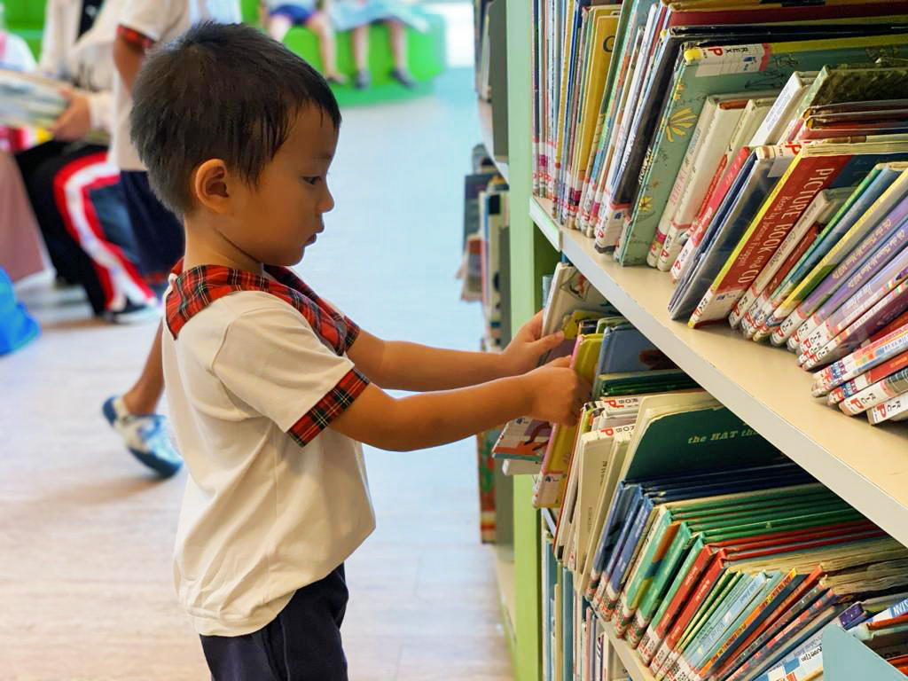 Our school outing! Preschool children going through books at the marine parade library (East Coast).