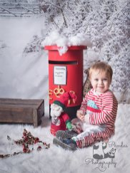 Little boy sitting by postbox