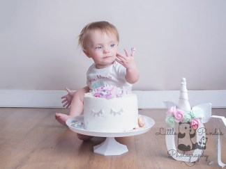 Little girl cake smash cake on fingers