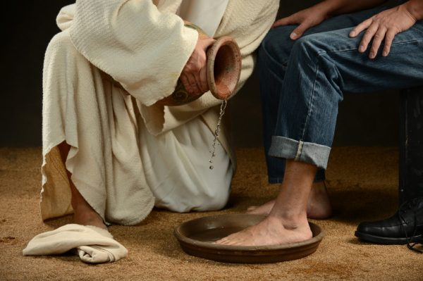 Foot washing ceremony - Jesus washing feet of person in jeans