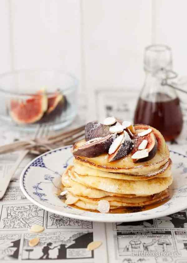 A stack of almond pancakes serves with figs, almonds and syrup