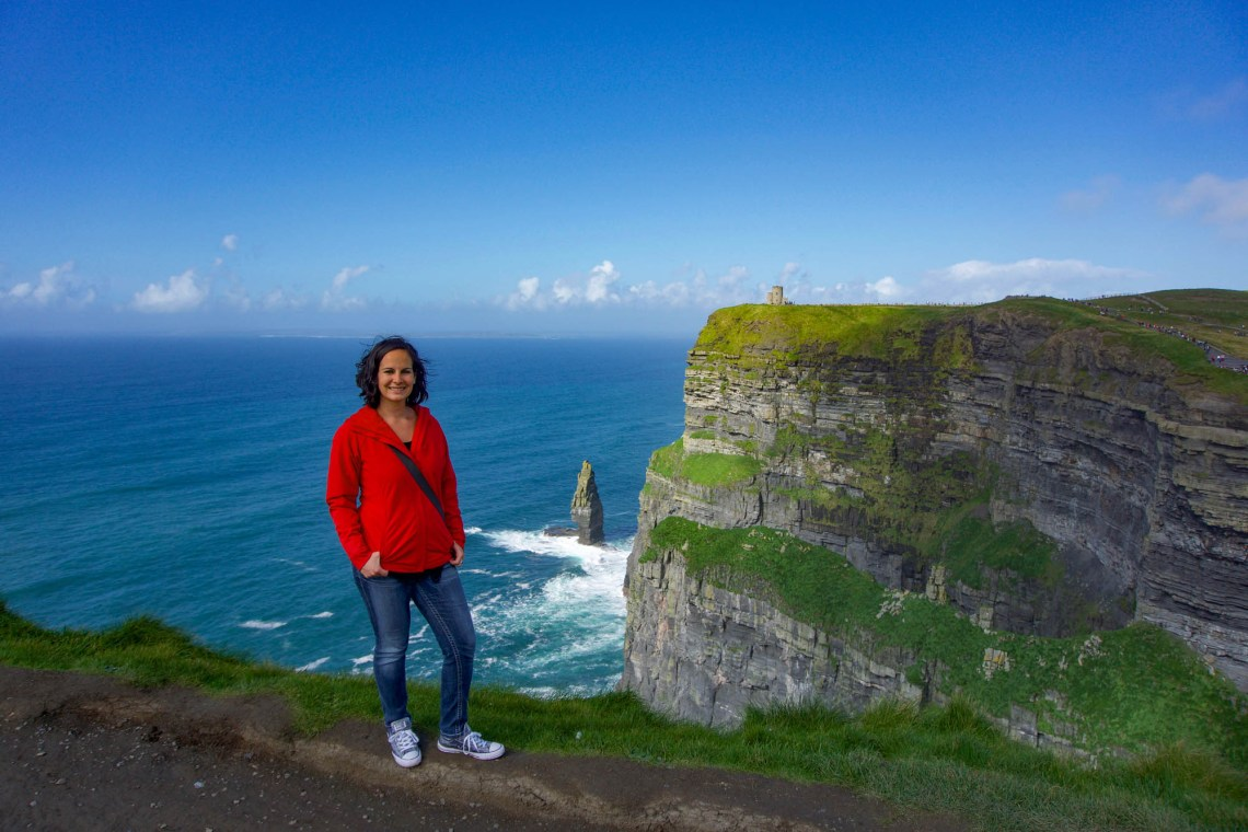 Woman in jeans and red jacket standing on grassy cliff with the ocean and green and brown cliffs behind her underneath a blue sky