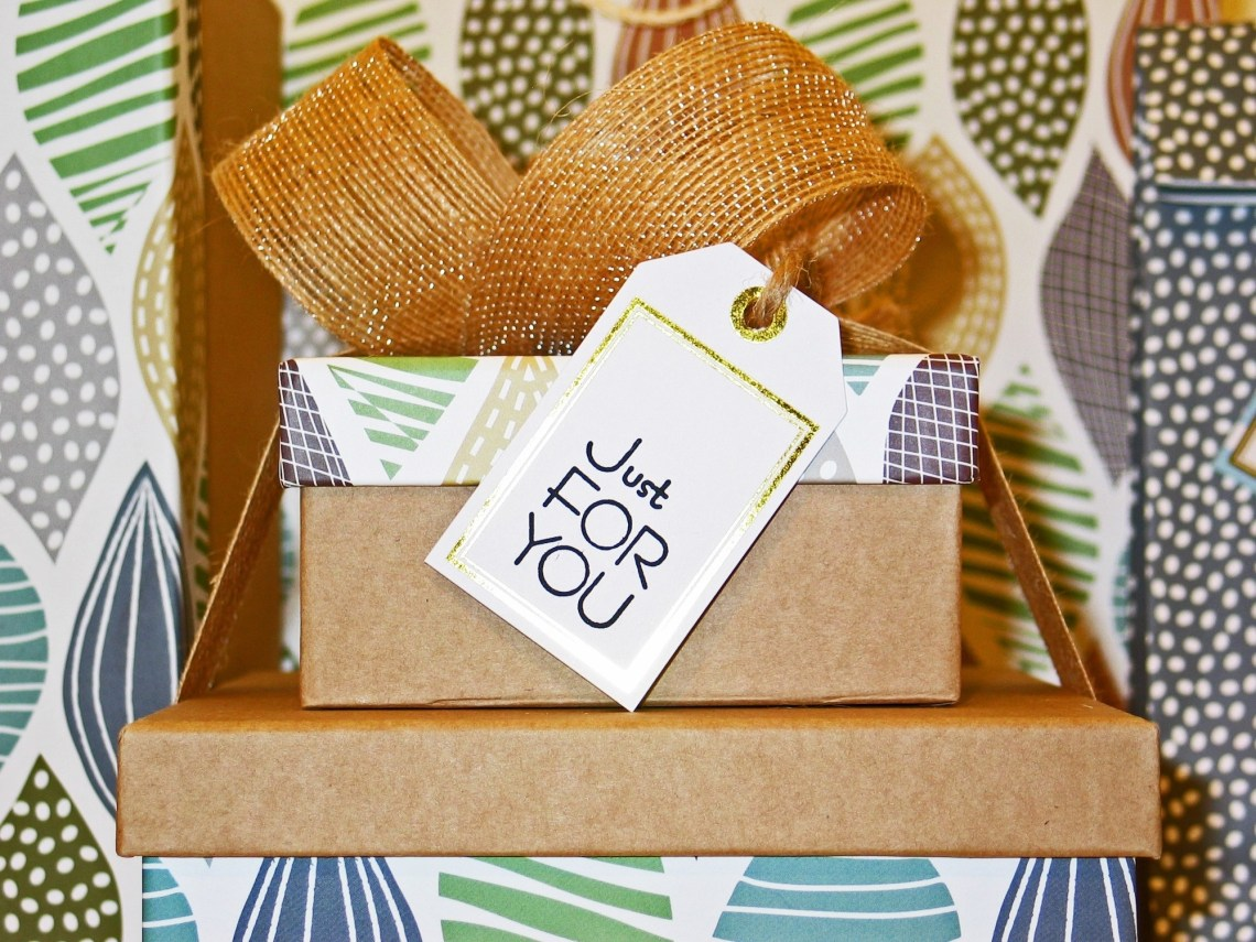 """Gift boxes stacked with a bow on top and tag that reads """"just for you"""""""