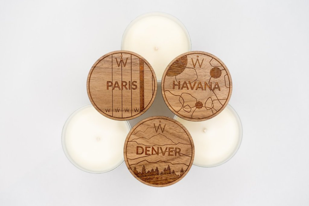 Three white candles with lids that read Paris, Havana, and Denver.