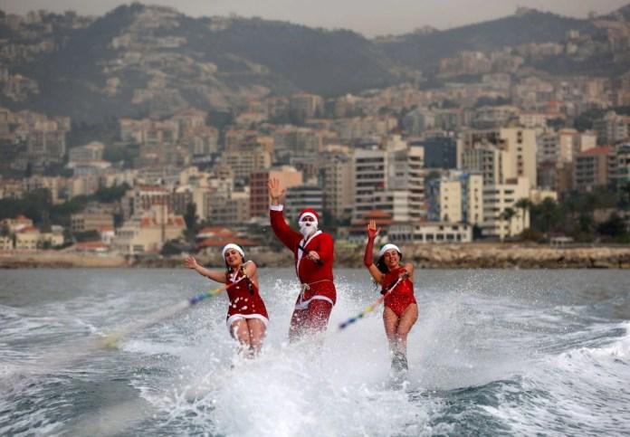 Участники ливанского клуба водных лыж выступают одетые в костюмы Санта Клауса в бухте Джуни, Ливан.