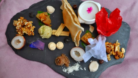 An assortment of traditional Thai desserts: pastries, fruits and sweet coconut soup garnished with edible flowers.