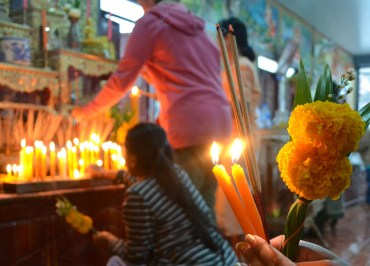 Buddhist Holy Days Almsgiving Ceremony at Temple with Candles, Incense and Flowers