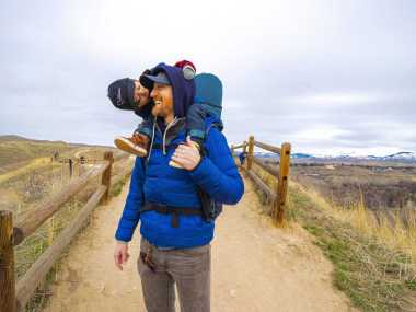 Man holding Toddler in carrier on hiking path