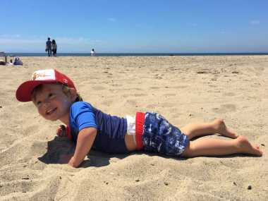 Toddler laying in sand on beach