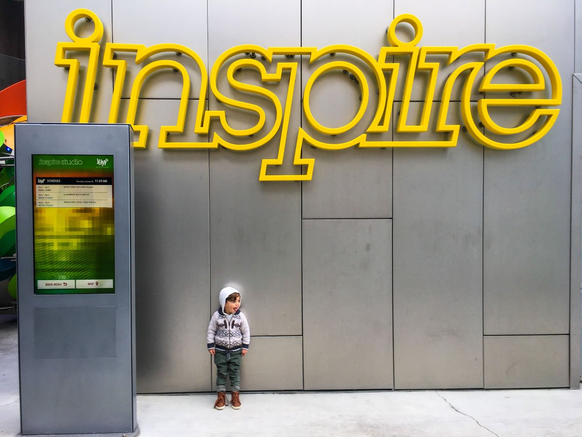 toddler standing in front of inspire sign