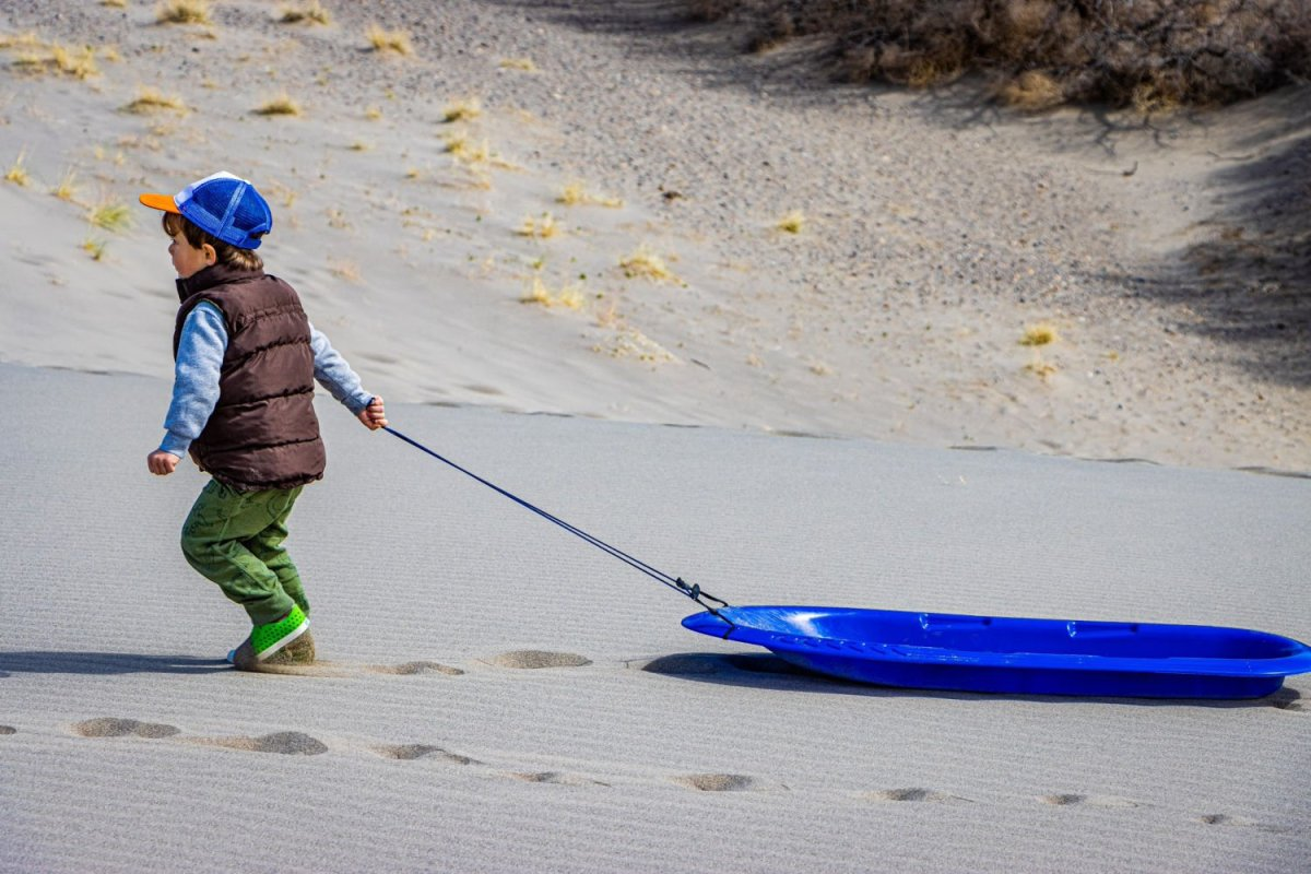 little boy pulling sled through sand dunes in Idaho