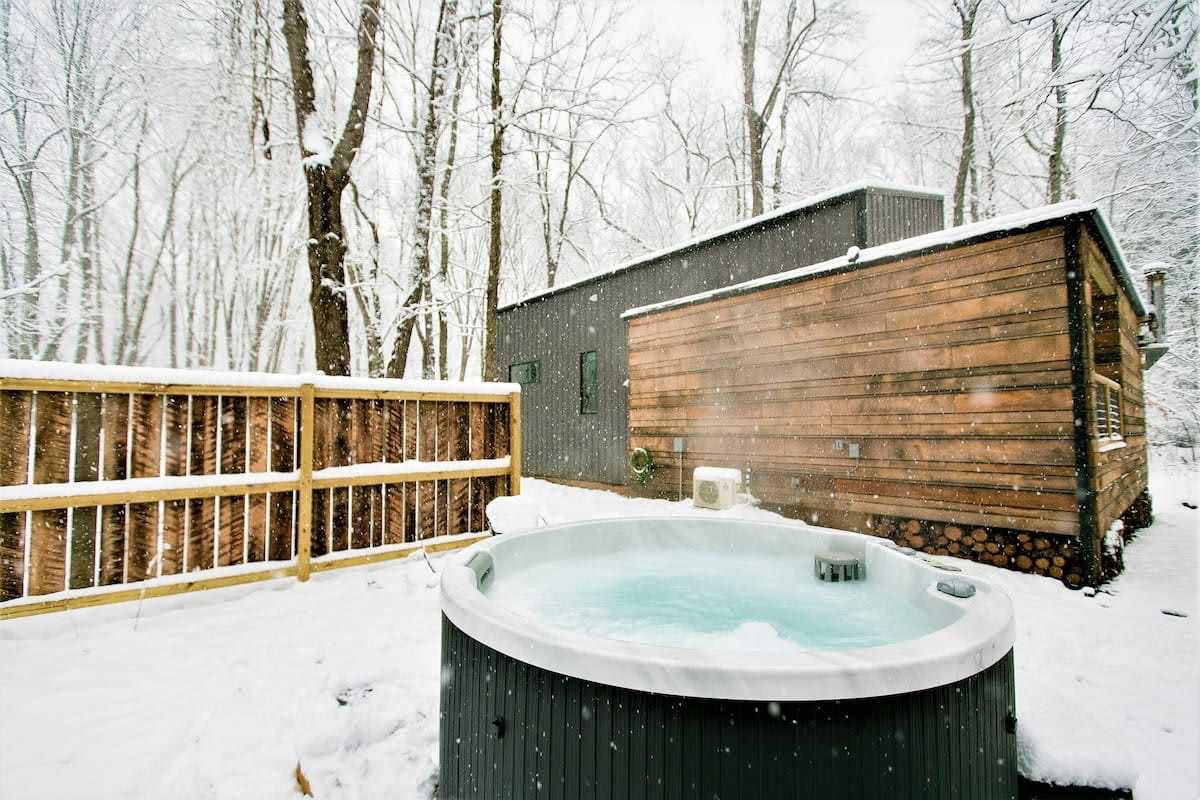 circular hot tub on a snowy day beside modern cabin