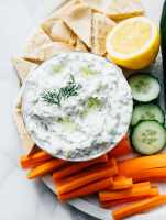 Best tzatziki recipe with pita bread and veggies on a marble table.