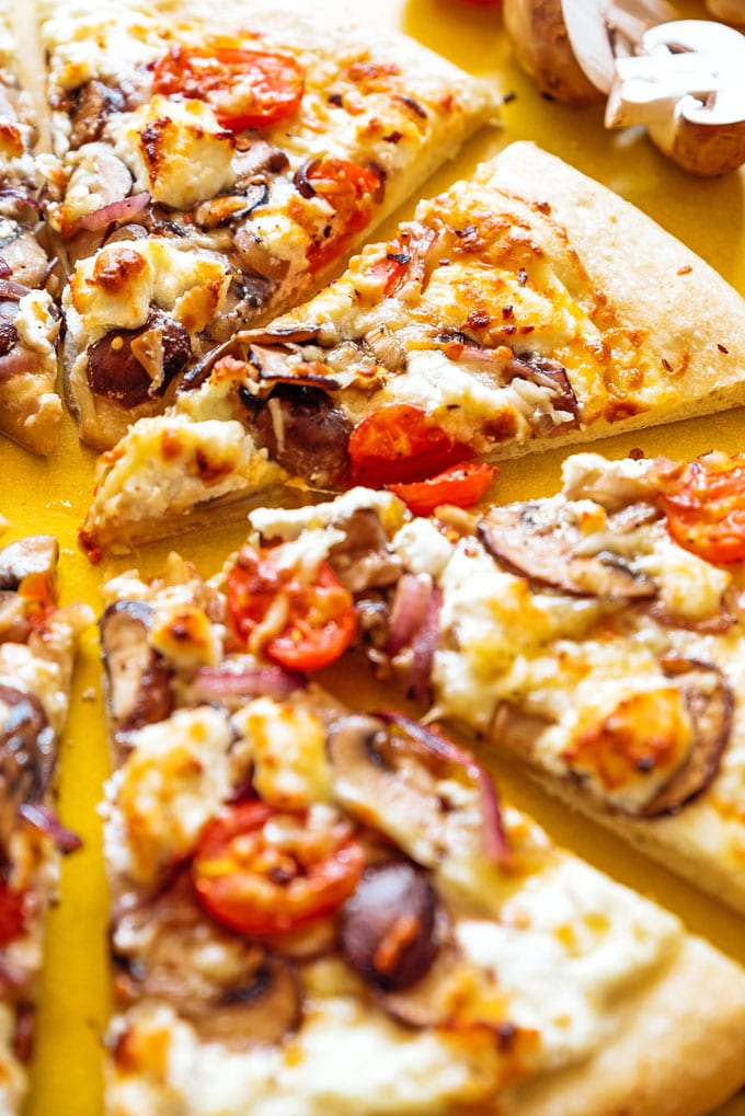 Goat cheese pizza slices on yellow background