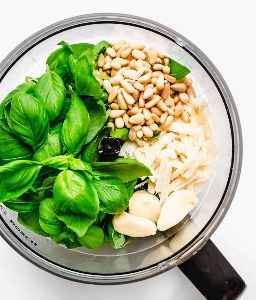 Ingredients to make pesto in a food processor