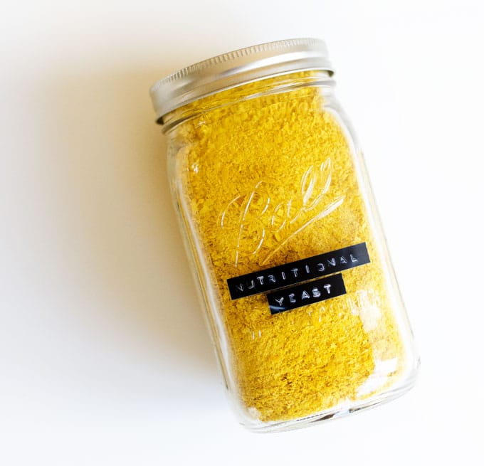 Jar of nutritional yeast on a white background