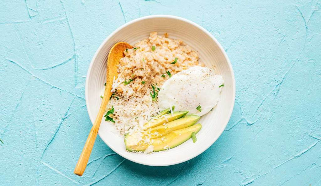 Oatmeal with egg and avocado in a white bowl on a blue background