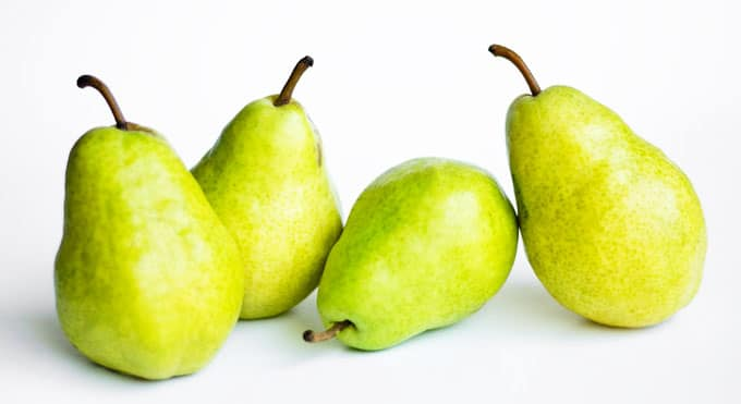 Green bartlett pear on a white background