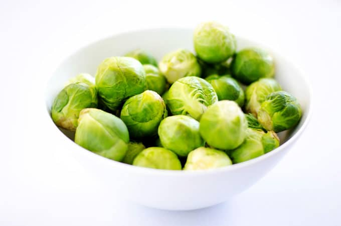 Brussels sprouts in a bowl on white background