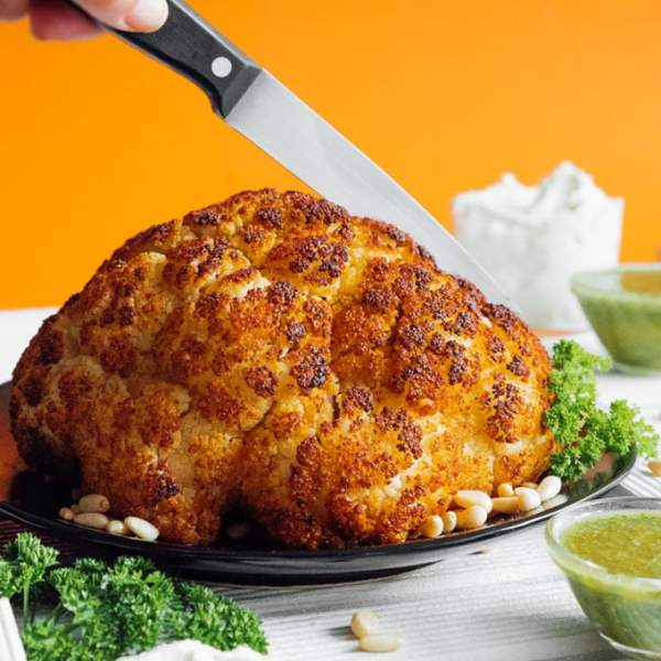 Whole roasted cauliflower with orange background