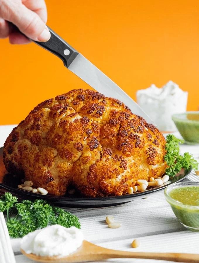 Whole roasted cauliflower with orange background