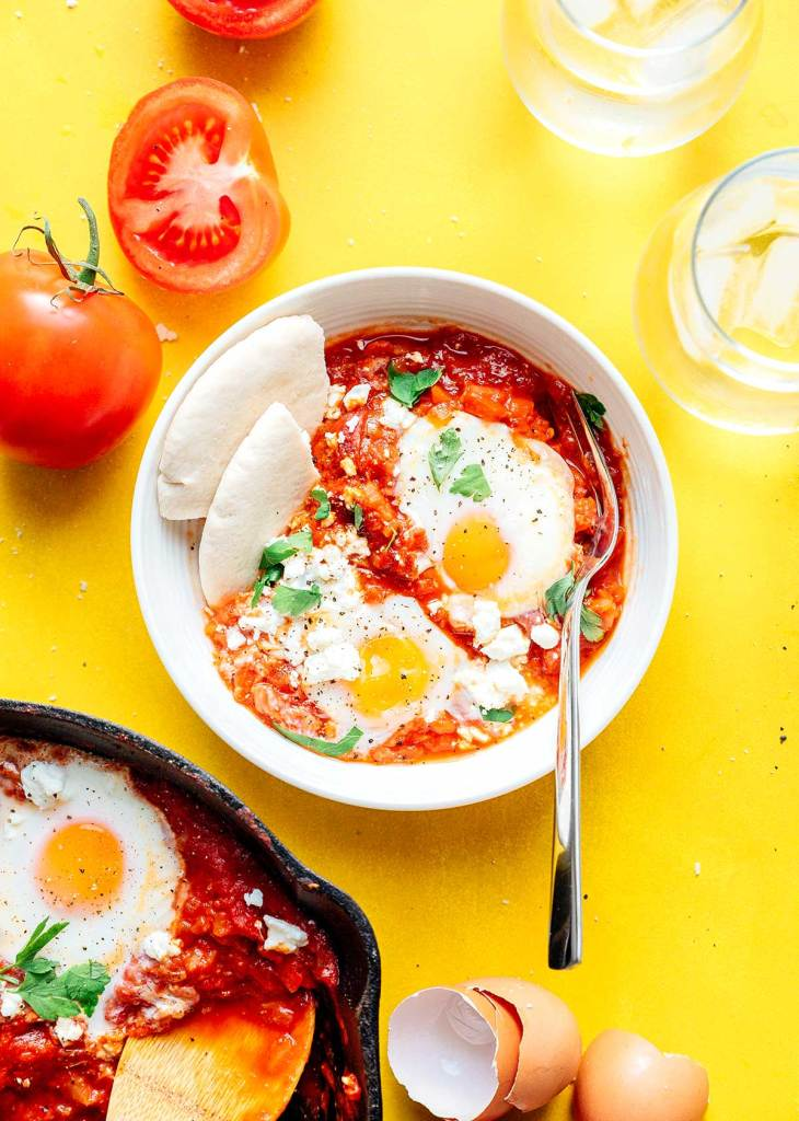 Shakshuka with eggs and pita break in a bowl on a yellow background