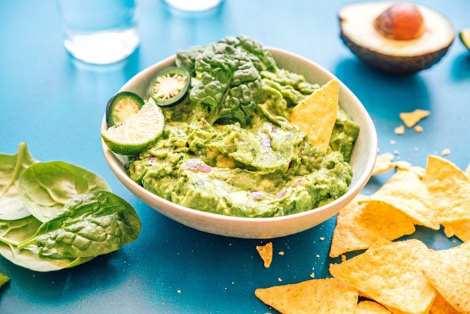 Healthy guacamole in a bowl with tortilla chips spinach